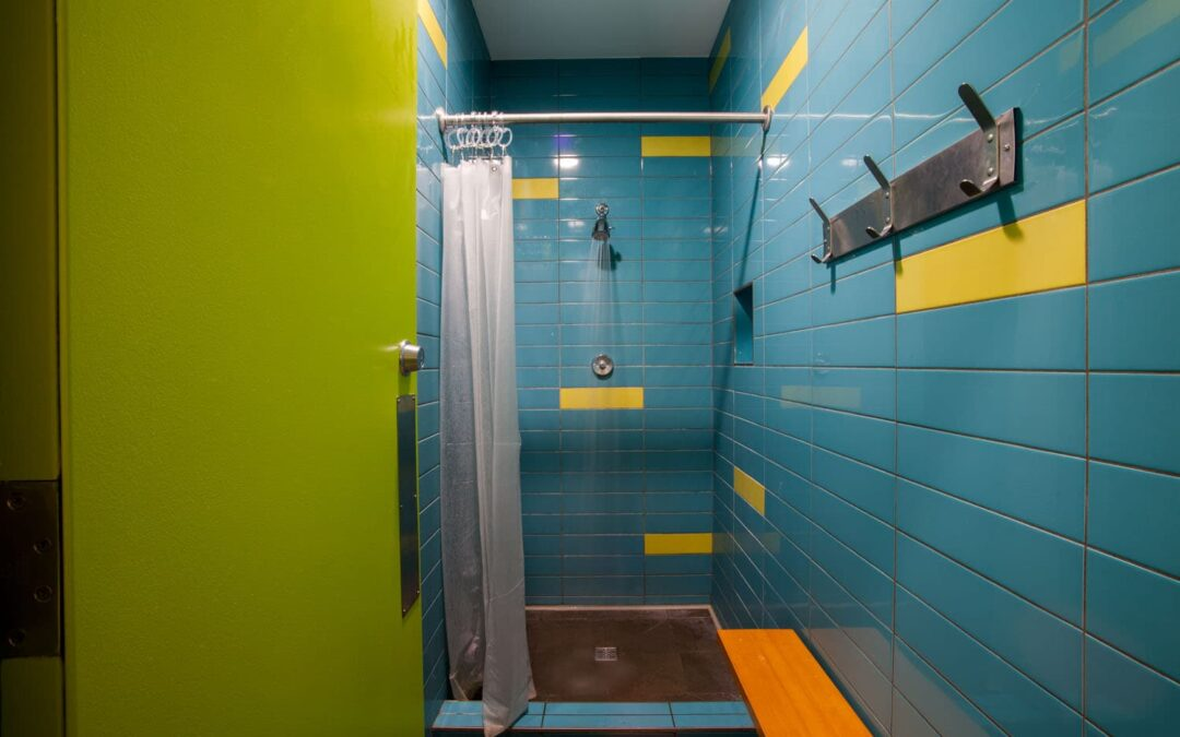 shower area with blue and yellow tiles
